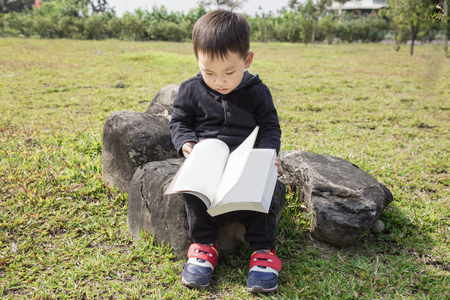 Smart kid is sitting on the rock and reading a book in the park