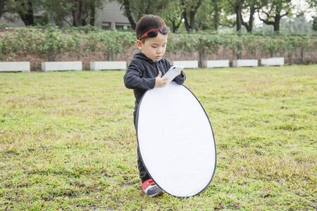 Funny little boy assist the photographer with reflector.