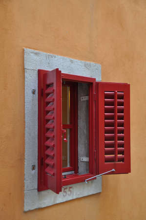 Red Window Shutters opened on a bright frame above a terracotta colored wall. The shutters unveil an also red lattice window. Underneath the window the house number 55 is painted.