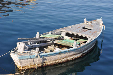 Old wooden fisher boat tied to buoys (not visible) in a Croatian harbor.  Inside the boat you can see a wooden mast and paddles plus fishing equipment. The water has a great blue tone and some reflection on tiny waves. Stock Photo - 5962008