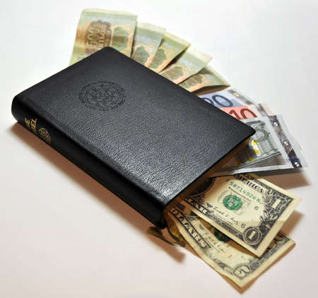 black leather bible with money (Dollars, Euro, Rubels) poking out