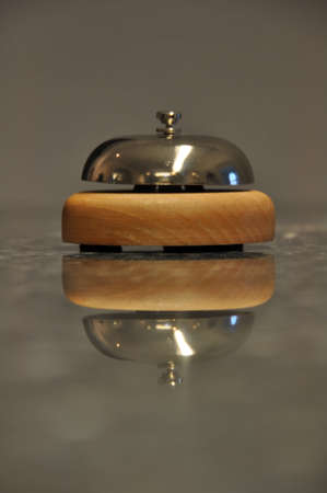 Detail shot of a service bell located on a hotel reception desk with great reflection on marble counter 版權商用圖片