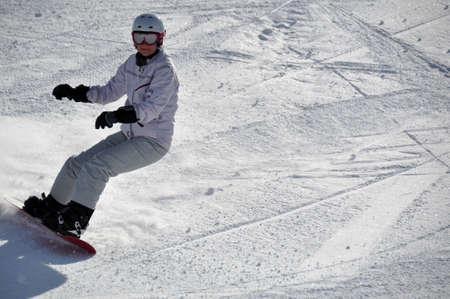 中間の老化させたメスのスノーボーダー パウダースノー リヴィーニョ、イタリアのアルプスで撮影 - 急な丘の上にヘルメットと雪のゴーグルを身に