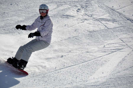 Middle aged female snowboarder wearing helmet and snow goggles in powder snow on steep hill - shot in Livigno, Italian Alps Stock Photo - 6570298
