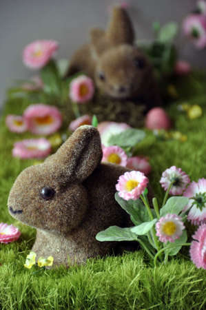faked: Easter decoration with rabbits, eggs and daisies on faked grass