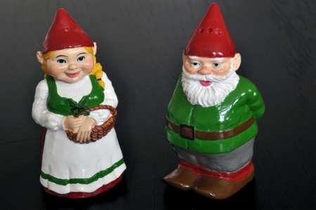 dwarfs: Cute set of salt and pepper shakers designed as dwarfs on dark wooden table