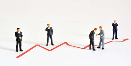 Group of managers (model railroad figures) positiones around graph showing rising development   Stock Photo