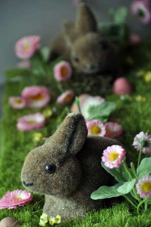 faked: Easter decoration with rabbits, eggs and daisies on faked grass..