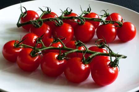 Fresh vine tomatoes  cherry tomatoes on white plate photo