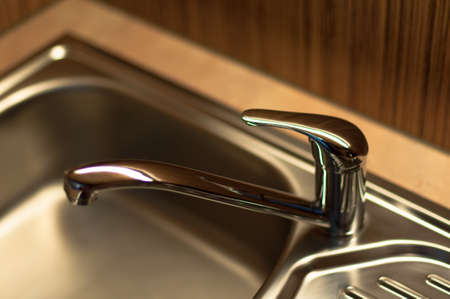 close-up of a chrome water faucet in a wooden kitchen photo