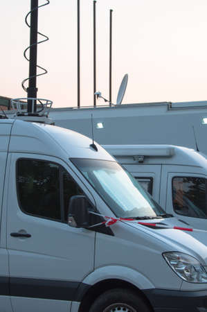 White broadcast trucks recording and broadcasting a live event photo