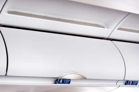 オーバーヘッドコンパートメント - 飛行機のキャビン インテリアの詳細ショット 写真素材