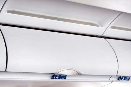 overhead: Overhead compartment - detail shot of an airplane cabin interior
