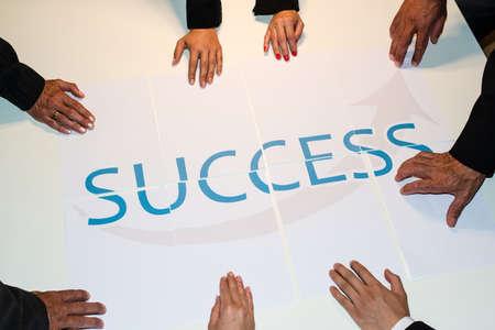 チームワークは成功を意味する: 単語成功を組み立てるビジネス人々 のグループがいくつかの論文に広がる - チームのサポートとヘルプの概念を表