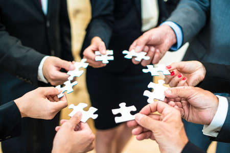 Teamwork - a group of eight business people assembling a jigsaw puzzle - representing team support and help concepts Stock Photo