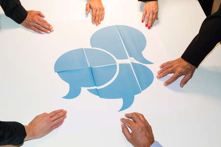 Communication: Hands holding pieces of a puzzle consisting of single papers with speech bubbles spread on them - concept for communication in teams, dialogue and understanding each other
