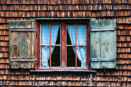 Idyllic Bavarian alpine cottage - window with curtains and wooden panels