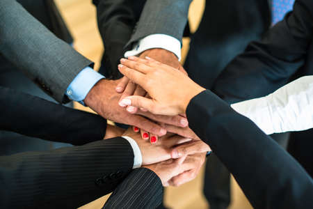 strong partnership: Multiracial group of nine diverse businesspeople standing in a circle facing each other joining hands in a team Stock Photo
