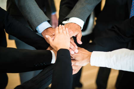 Multiracial group of nine diverse businesspeople standing in a circle facing each other joining hands in a team Stock Photo
