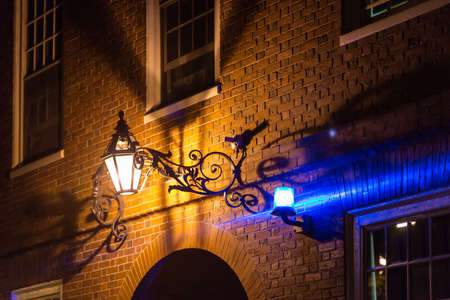 Alleyway by night with blue security light on brick wall photo
