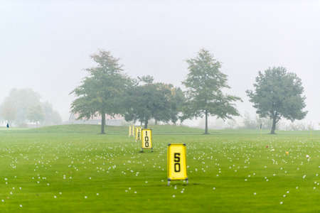 driving range: Yard signs in driving range and golf balls Stock Photo