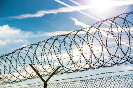素晴らしい青空の自由、自由または刑務所の概念の前に有刺鉄線のフェンス 写真素材