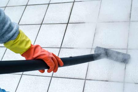 mujer limpiando: Mujer que usa el limpiador de vapor