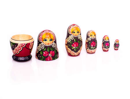 Russian nesting dolls ( babushkas or matryoshkas ) with reflection and shadows on white background