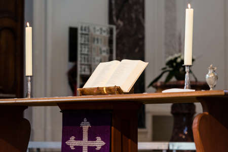 Open Bible and candles on the altar of a church