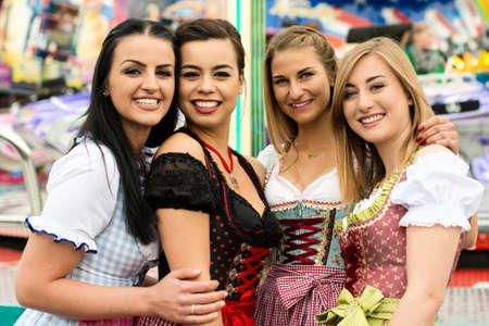 octoberfest: 4 gorgeous young women at German funfair