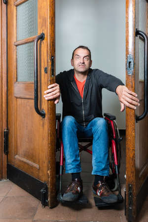 Man in wheelchair stuck between swing doors