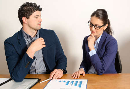 businessman talking: two young business people discussing