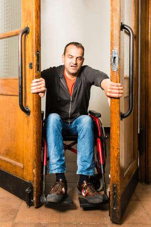 Man in wheelchair stuck between swing doors photo