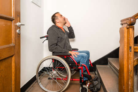 drawback: man in wheelchair facing a barrier of stairs