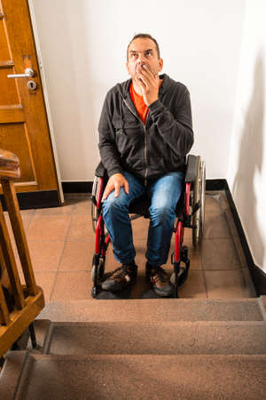 unreachable: man in wheelchair facing a barrier of stairs