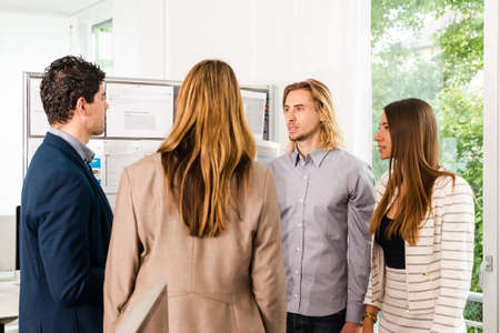 might: Businesspeople looking at bulletin board in office and discussing designs pinned at it. Mixed caucasian group rather casual, might be a startup comany or a creative agency.