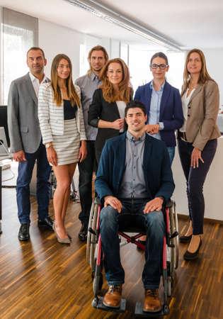 Porträt eines Business-Team im Büro, ein Mann sitzt in einem Rollstuhl, alle ziemlich jung - vielleicht ein Startup-Unternehmen zu sein