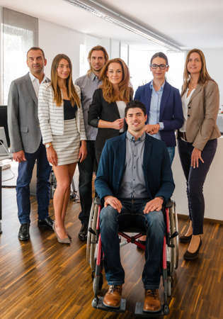 integrated group: Portrait of a business team inside the office, one guy sitting in a wheelchair, all rather young - might be a startup company Stock Photo