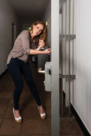 handcuffed: Tied to the office - Attractive business woman is strapped to metal office doors with handcuffs - trying to free herself in panic Stock Photo