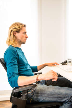 careerists: Tied to the office - Young handsome business guy strapped to chair with handcuffs in front of his computer in a modern office Stock Photo