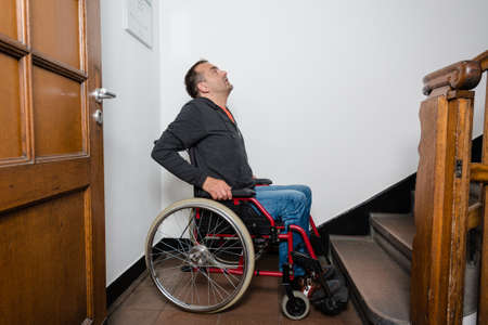 drawback: a disabled man in a wheelchair is facing a barrier of stairs, looking as if in panic and dismay Stock Photo