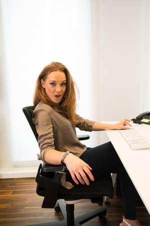 tied: Gebunden an das Büro - Junge schöne Geschäftsfrau auf Stuhl mit Handschellen vor ihrem Computer in einem modernen Büro geschnallt Lizenzfreie Bilder