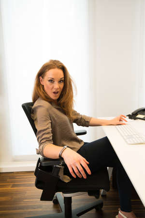 woman in handcuffs: Tied to the office - Young beautiful business woman strapped to chair with handcuffs in front of her computer in a modern office
