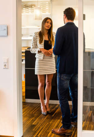 Office interior - a visitor is being picked up by an attractive female receptionist in a modern design environment - might be a startup or a creative agency Stock Photo