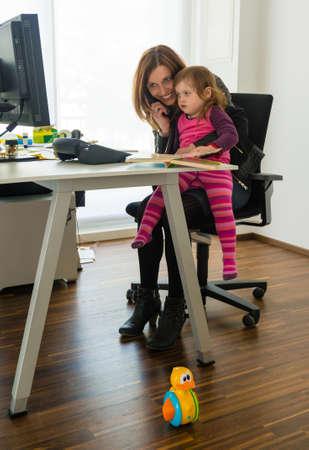 家族および仕事の生命の和解: フォア グラウンドでおもちゃで彼女の膝の上に座っている小さな娘が気を取られてビジネス装いで魅力的な女性