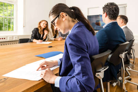 ambiente: An attractive young woman is checking papers during a business meeting in a conference room - mixed caucasian team rather casual, ambiente might suggest a startup or an agency