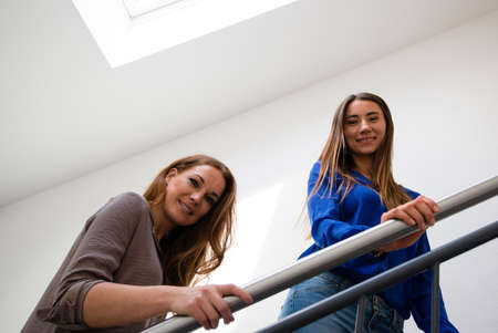 upper floor: Waist shot of two young female colleagues on the staircase of an office Stock Photo