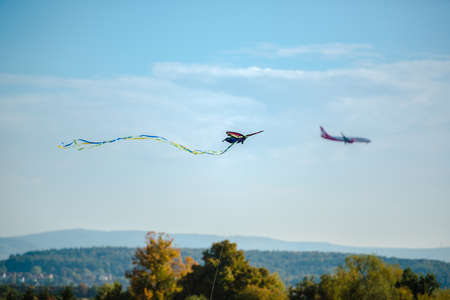 overtaken: A colorful kite is being overtaken by an airplane approaching Stuttgart airport in Germany