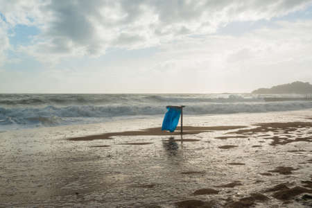 uncluttered: Trash can with blue bag in the waves during high tide on the beach