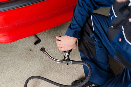A mechanic is applying a diagnostic sensor to the exhaust of a red car, measuring the composition and substances in the exhaust fumes in a garage
